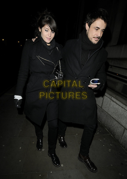 """GEMMA ARTERTON & GUEST (fiance STEFANO?).Departed after the First Night evening performance of """"The Little Dog Laughed"""", GarrickTheatre, London, England, UK, 9th January 2010 .full length black coat gloves trousers walking arm around shoulder zip trench belt belted .CAP/CAN.©Can Nguyen/Capital Pictures"""