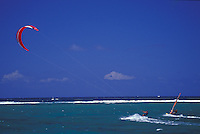 Kite surfer and sail boarder racing in clear lagoon waters off Anini Beach, east side of Kauai