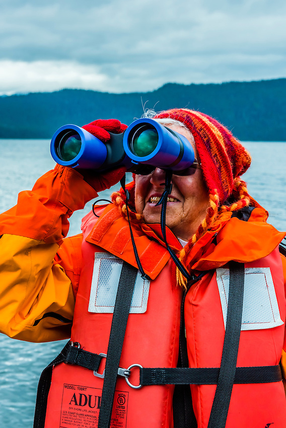 Elderly passenger looking at wildlife through binoculars on a skiff excursion from the Wilderness Explorer, Patterson Bay, Chichagof Island, Inside Passage, Southeast Alaska USA.