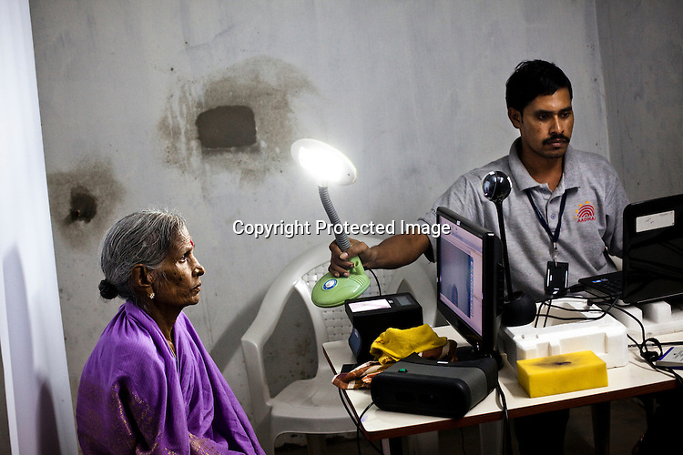 An official assists an old woman to have her photo taken as part of the enrollment that is on its way in Naagaaram village, outskirts of Hyderabad in Andhra Pradesh, India. India is assigning each one of its 1.2 billion people a unique ID number based on digital finger prints and iris scan. Photograph: Sanjit Das/Panos