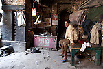 Resident squatter Sanjay (14, no last name) sits on his bed housed in an unnamed Lodhi period tomb in Zamroodpur, Delhi, India. It has fallen into disrepair and has subsequently been turned into a de facto cow shed, rubbish dump and slum as the surrounding suburb has encroached upon it.The Archaeological Survey of India has been on a campaign to evict people who have illegally made heritage tombs their homes throughout the city in recent times but is facing stiff opposition from the residents. The area is littered with tombs that need excavation.