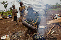 A grandmother prepares lunch for her grandchildren in Nyori refugee camp, South Sudan. The are refugees from LRA attacks in the border area of  Congo.
