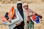 Women carry a tarp, blankets and other items that they received from Christian Aid in the Jamtoli Refugee Camp near Cox's Bazar, Bangladesh. Christian Aid is a member of the ACT Alliance.<br /> <br /> More than 600,000 Rohingya have fled government-sanctioned violence in Myanmar for safety in Bangladesh.
