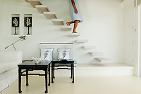 The cantilevered staircase floats down into the pristine white living room furnished with black lacquered tables