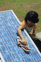 Indien Karnataka, Junge reinigt Shell Solarzellen in Solar workshop / India Karnataka, cleaning of solar cell in solar workshop