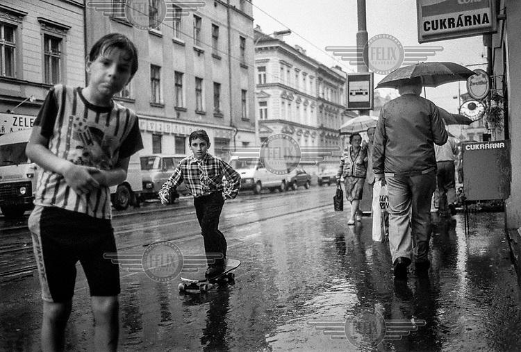 A boy rides a skateboard along Seifertova Street during a downpour.