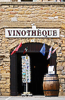 A wine shop vinotheque with flags, post cards on a stand and a barrel with wine bottles. Chateauneuf-du-Pape Châteauneuf, Vaucluse, Provence, France, Europe Chateauneuf-du-Pape Châteauneuf, Vaucluse, Provence, France, Europe