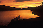 Orange sky after sunset silhouettes a canoe on the shore of the Missouri River in Montana