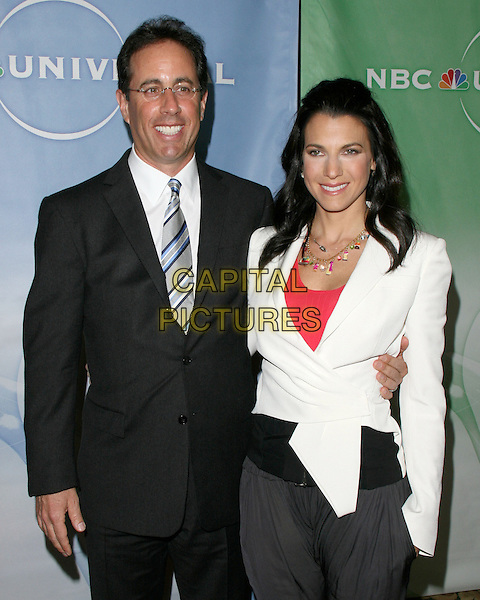 JERRY & JESSICA SEINFELD .at NBC Universal's Press Tour Cocktail Party held at The Langham Huntington Hotel & Spa in Pasadena, California, USA, January 10th 2010.                                                                   .half length glasses black suit tie white jacket husband wife married blue striped couple .CAP/RKE/DVS.©DVS/RockinExposures/Capital Pictures.
