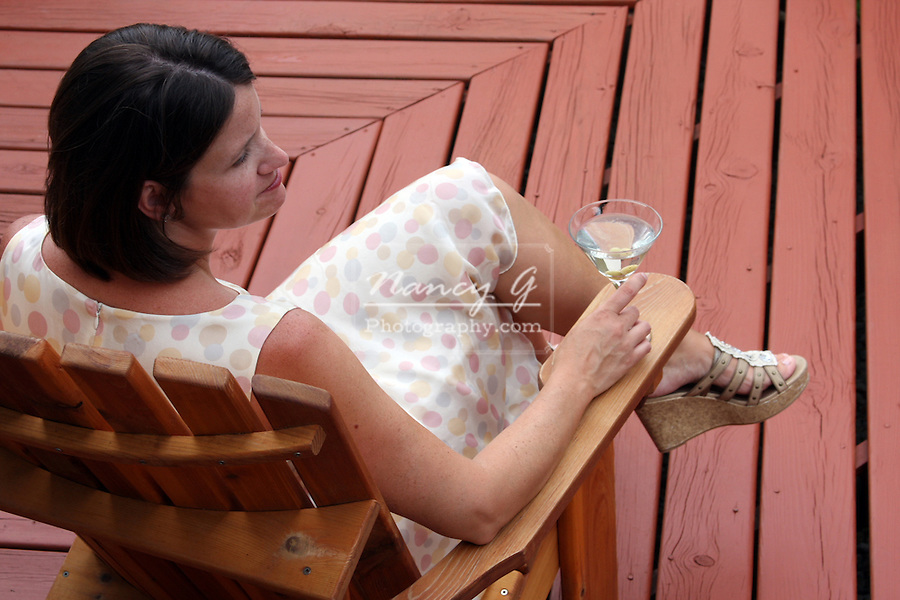 A woman having a martini drink on a deck