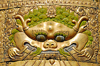 The Face of Majesty, or monster of greed, devouring a net of jewels, traditional detail on cylindrical victory banner, at each corner of a monastery roof,  symbolizing Buddha's triumph over the four Maras, or evils, Jokhang Temple, Lhasa, Tibet, China.
