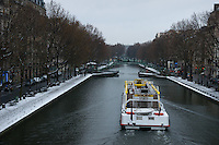 Bateaubus travelling along Canal St Martin in Paris in the snow.