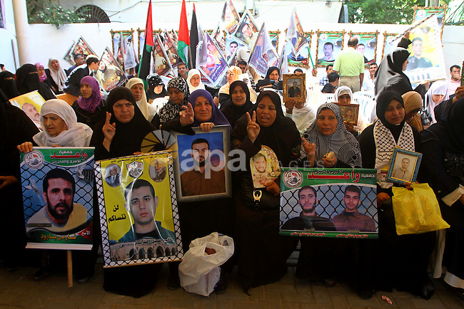Palestinians hold pictures of their jailed relatives during a protest outside the Red Cross' offices in Gaza City calling for the release of Palestinian prisoners held in Israeli jails, on June 20, 2011. Photo by Ashraf Amra