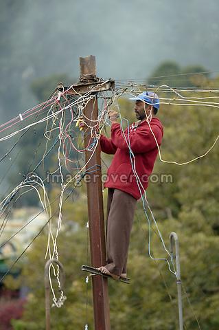 India, Tamil Nadu, Coonoor 2005. Indian electrician working on wiring post in Coonoor.
