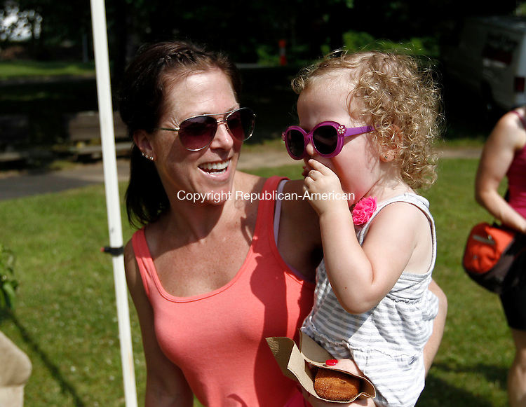 Southbury, CT- 03 July 2014-070314CM14-  Colleen Geel, left, of Southbury, smiles as her daughter Ellie Geel, 2, enjoys an apple cinnamon donut during the Town of Southbury's Farmer's Market in Southbury on Thursday.  The market runs through the summer on every Thursday at the Southbury Town Hall.  Christopher Massa Republican-American