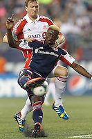 New England Revolution forward Dimitry Imbongo (92) passes the ball as Toronto FC defender Steven Caldwell (13) pressures. In a Major League Soccer (MLS) match, Toronto FC (white/red) defeated the New England Revolution (blue), 1-0, at Gillette Stadium on August 4, 2013.