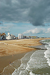 Panoramic view looking over Eastbourne beach, with seafront buildings and dramatic sky in the distance