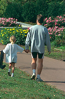 Father and daughter ages 30 and 6 strolling through park. Catholic School Bike-A-Thon  St Paul  Minnesota USA