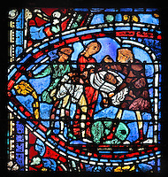 The younger son is threatened with a stick and robbed of his clothes and his last possessions, from the Parable of the Prodigal Son stained glass window, in the north transept of Chartres Cathedral, Eure-et-Loir, France. This window follows the parable as told by St Luke in his gospel. It is thought to have been donated by courtesans, who feature in 11 of the 30 sections. Chartres cathedral was built 1194-1250 and is a fine example of Gothic architecture. Most of its windows date from 1205-40 although a few earlier 12th century examples are also intact. It was declared a UNESCO World Heritage Site in 1979. Picture by Manuel Cohen