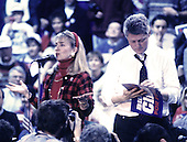 "Hillary Rodham Clinton, left, speaks at a campaign rally at Fairgrounds Junior High School in Nashua, New Hampshire as her husband, Governor Bill Clinton (Democrat of Arkansas), right, signs autographs on February 16, 1992.  The Clintons were campaigning in advance of New Hampshire's ""First in the Nation"" presidential primary.<br /> Credit: Ron Sachs / CNP"