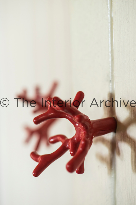 A simple built-in cupboard in the living room has sculptural coral handles