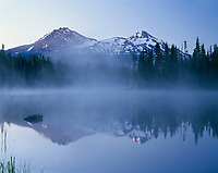 ORCAC_111 - USA, Oregon, Willamette National Forest, North (left) and Middle Sister (right) reflect in Scott Lake at dawn while fog rises above the lake.