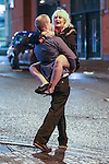 © Joel Goodman - 07973 332324 . No syndication permitted . 01/01/2014 . Manchester , UK . A man carries a woman who's clutching a rose . Revellers see in the New Year in Manchester today (January 1st 2014) as police report that officers are at full stretch responding to calls . Photo credit : Joel Goodman