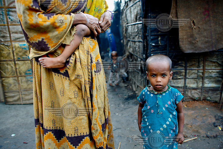 A woman and her young children in one of the city's slum districts. It is thought that more than six million people live in slums in Dhaka.