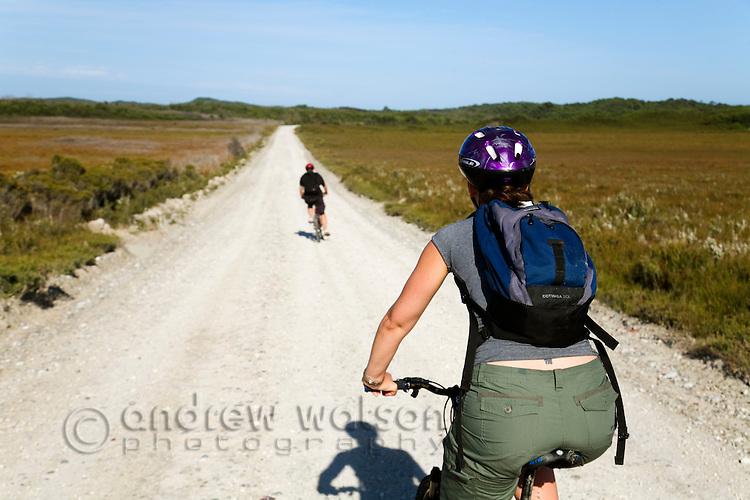 Mountain biking along a dirt road to Ocean Beach.  Strahan, Tasmania, AUSTRALIA