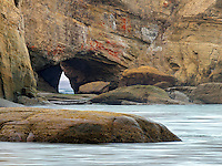 Beach with arch and light of boat in arch at Devil's Punchbowl State Natural Area. Oregon