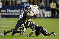 17 September 2011:  FIU defensive back Tevin Blanchard (29) combines with defensive back Richard Leonard (3) to bring down UCF running back Brynn Harvey (34) in the second half as the FIU Golden Panthers defeated the University of Central Florida Golden Knights, 17-10, at FIU Stadium in Miami, Florida.