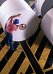 Workman hammering core into paper roll