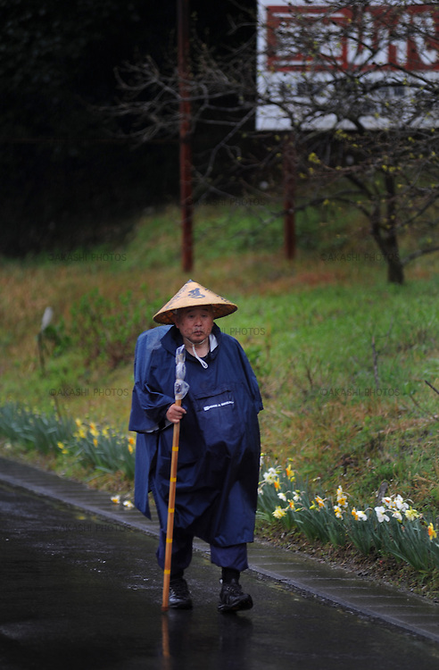 Henro pilgrim walking towards a temple on a rainny day. Shikoku. Japan.