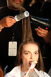 A model eats as she has her hair styled backstage before the Banana Republic presentation during New York Fashion Week in New York, Saturday, September 12, 2015. AFP PHOTO/TREVOR COLLENS