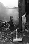 Toxteth, Liverpool. 1981<br /> Greengrocers scales lie abandoned outside a burnt out shop, as residents look on in disbelief at what has happened to their neighbourhood.
