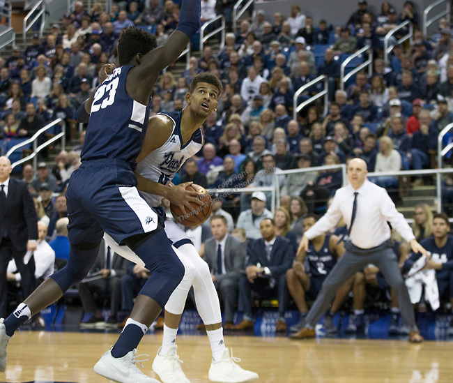 Nevada forward forward Trey Porter (15) looks to shooot over Utah State center Neemias Queta (23) in the first half of an NCAA college basketball game in Reno, Nev., Wednesday, Jan. 2, 2019. (AP Photo/Tom R. Smedes)