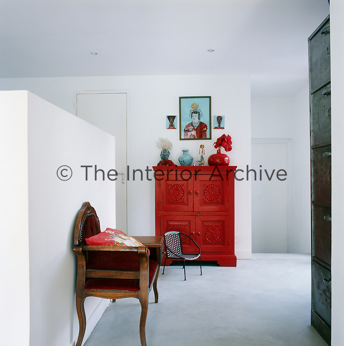 The white walls act as a neutral backdrop and allow the bold accent colours of the furniture and furnishings to come to the fore, such as a brightly painted red cabinet and a red upholstered period seat.