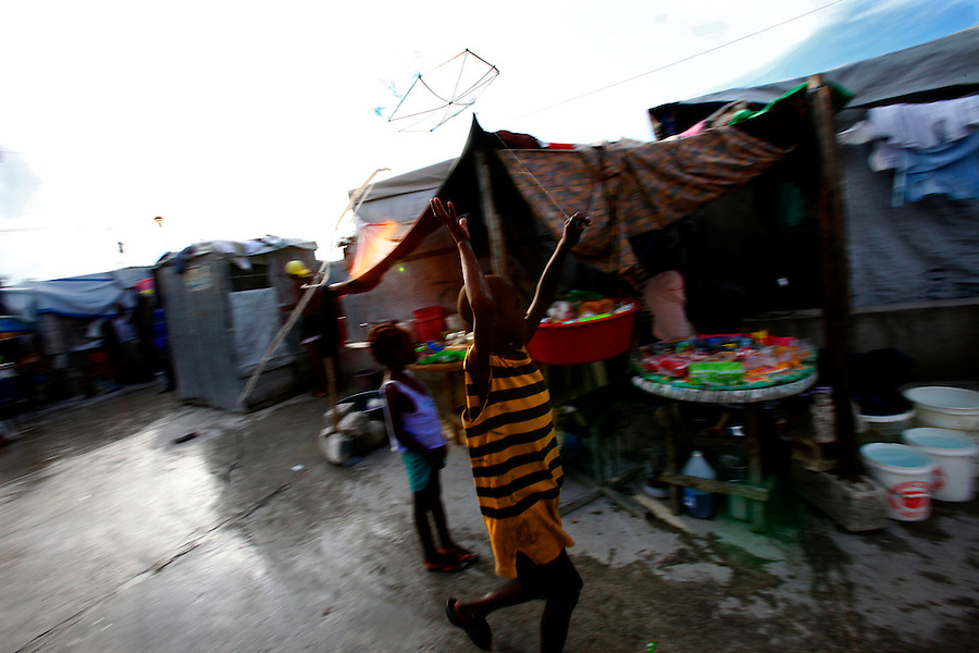 Nov 10, 2010 - Port-au-Prince, Haiti.A young resident of one of the many tent cites in Port-au-Prince, Haiti plays with a kite on the wet pavement near a water distribution site on Wednesday, November 10, 2010 as fears of a Cholera outbreak spread through the area just two days after cases of the infection were confirmed in the Haitian capital. Officials from the Pan American Health Organization warn that Haiti's cholera epidemic, spread primarily through consuming infected water and food, is likely to grow much larger in the wake of Hurricane Tomas.  (Credit Image: Brian Blanco/ZUMA Press)