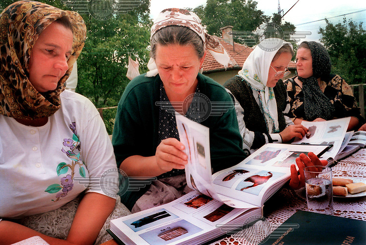 BOSNIA & HERCEGOVNA. Hadzici. 21/07/2000..Women from Srebrenica lok through an identification book produced by the Red Cross showing photographs of the belongings of 354 unidentified men exhumed in the region around Srebrenica..©Andrew Testa for the New York Times.