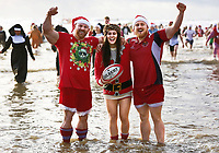 Pictured: Three people wearing a combination of Santa and rugby outfits take to the water. Tuesday 26 December 2017<br /> Re: Hundreds took part in this year's Boxing Day Walrus Dip which see people in fancy dress taking to the sea at Cefn Sidan beach in Pembrey Country Park, west Wales, UK.