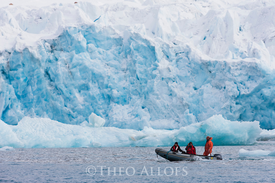 Norway, Svalbard, tourists cruising in Zodiak in front of glacier