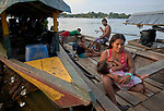 Indigenous people live in their canoes on the Javari River at Atalaia do Norte in Brazil's Amazon region. They travel several days from their villages upstream in order to access government services such as health care in the town.