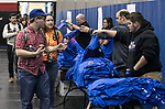 Matt Merkt and Frank Kreutzer (right) hand out New Student Service Day t-shirts as freshmen and incoming students gather in DePaul's McGrath-Phillips Arena Tuesday, Sept. 5, 2017. Students fanned out across the city to volunteer at dozens of community organizations following the early morning rally on the Lincoln Park Campus. (DePaul University/Jamie Moncrief)