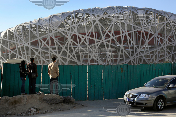 "A family looking over the fence to the 2008 Olympic Games' ""Bird's Nest"" stadium."