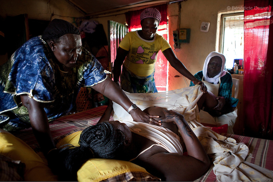 July 18, 2011 - Juba, Republic of South Sudan - Lushi Rashid, a 29 year old muslim South Sudanese woman, gives birth to her fifth child at her family home with the help of her mother Marcelina Dudu (L), her aunt and Regabia Ahmad (R), a qualified birth attendant, in Juba, the capital city of South Sudan. Regabia has been delivering babies in South Sudan for over twenty years. she was trained by the health ministry and works at a local primary health clinic. With fewer than 100 trained midwives for a population of over eight million, South Sudan has the highest maternal mortality rate in the world.  One in seven South Sudanese women is likely to die because of complications from delivery. Just 10 per cent of South Sudanese women have access to medical professionals during childbirth. Photo credit: Benedicte Desrus