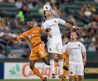 LA Galaxy forward Alan Gordon (21) beats Puerto Islanders Christopher Nurse (8) to a headball. The Puerto Rico Islanders defeated the LA Galaxy 4-1 during CONCACAF Champions League group play at Home Depot Center stadium in Carson, California on Tuesday July 27, 2010.