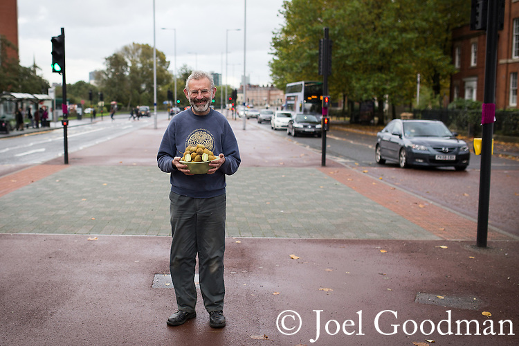 &copy; Joel Goodman - 07973 332324 . 24 August 2013 . Manchester , UK . Alain with the freshly picked kiwifruit harvest, in the busy A6 road in front of the library where he grew the vine.<br /> <br /> The stunning summer has brought an astonishing crop of exotic kiwifruit for one gardener - beside a busy main road in Manchester.<br /> <br /> Green-fingered Alain Kahan grew the exotic &quot;Actinidia deliciosa&quot; - or &quot;Fuzzy Kiwifruit&quot; - vine from scratch after buying a punnet of the fruit from a Manchester Asda in 1989 and cultivating the plant in the small garden of the library where he worked.<br /> <br /> &quot;I blended the pulp with water and allowed the seeds to separate before planting them out&quot; says Alain.<br /> <br /> Alain has since retired but, despite having only a small patch of land in which to grow and no greenhouse for protection, the vine has thrived and this year's long, hot summer has delivered a stunning haul of supermarket-sized kiwis, more typically found growing in the warmer climbs of Italy and New Zealand.<br /> <br /> The fruit grows well in areas where there are no frosts to damage the flesh. According to Alain, the long, warm spell was just what was needed. &quot;Last year's early frost turned the fruit to mush but the long summer meant I could wait that bit longer - this year's been perfect for them&quot;.<br /> <br /> Retired Librarian Alain was so surprised at the size of the crop, that he's kept the vine's location a closely-guarded secret. Fortunately fears that the furry fruit would be stolen from the roadside before they ripened have proved unfounded and Alain's now harvesting bowlfuls of the fruit, which he says he'll share with colleagues and friends at the library in Salford, where he still helps out two days a week.<br /> <br /> &quot;They have a better taste than the ones from the Supermarket&quot; insists the sixty-five year old amateur gardener, &quot;it must be something in the Salford soil&quot;.<br /> <br /> The home of the kiwifruit can be traced to southern China, only arriving in New Zealand at the turn of the twentieth century, where the frost-free climate