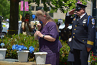May 10, 2013  (Washington, DC)  A loved ones of a fallen officer enjoys a flower before dedicating it to a fallen officer during a ceremony at the Washington Area Law Enforcement Memorial.  (Photo by Don Baxter/Media Images International)
