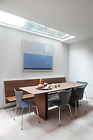 The dining area, furnished with a matching angular table and built-in bench, is lit from above by a rectangular skylight, while an abstract painting adds an inoffensive soft blue to the minimal design scheme