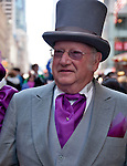 A man in the New York City Easter Parade wearing a gray suit, a purple tie, and a top hat